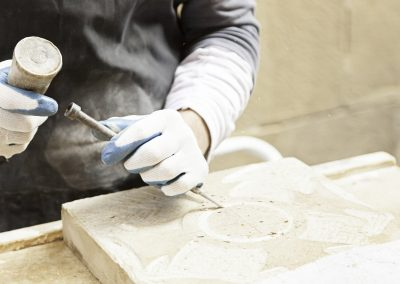 A stonemason carving into stone.